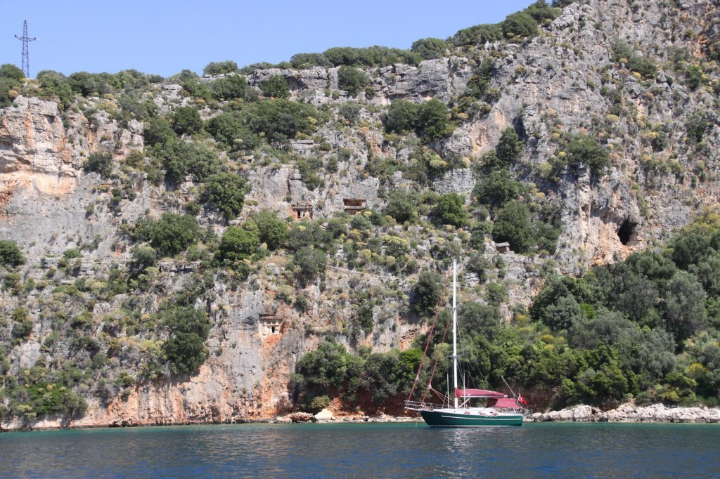 A Yacht Moored by Some Ancient Tombs Carved into the Rock Cliffs