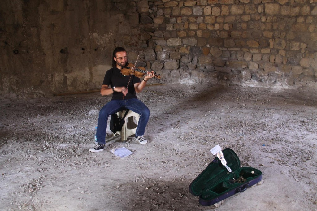 A Clever Musician Busks in the Cool Ancient Tower at the Port Entrance to the Market