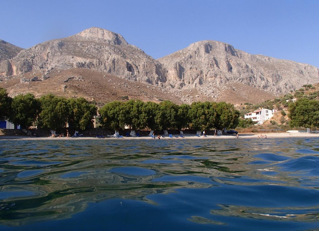 The Small Beach in the Town is Shadowed by Tall Mountains in the Distance