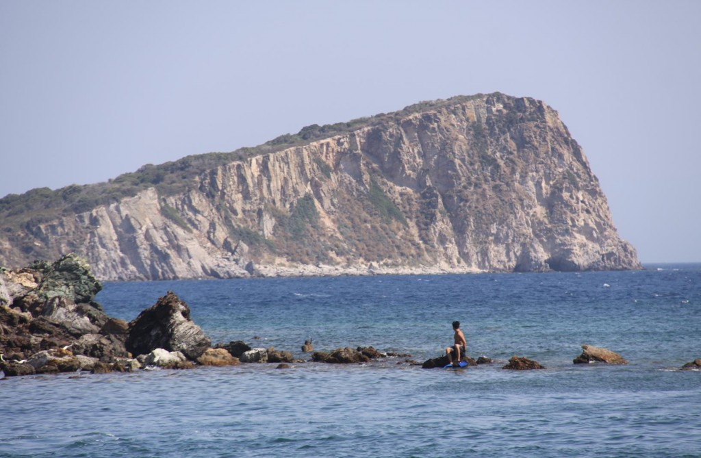 A Lone Swimmer from the Beach Looks Back at Doganbey Adasi, the Wedge Shaped Island Nearby