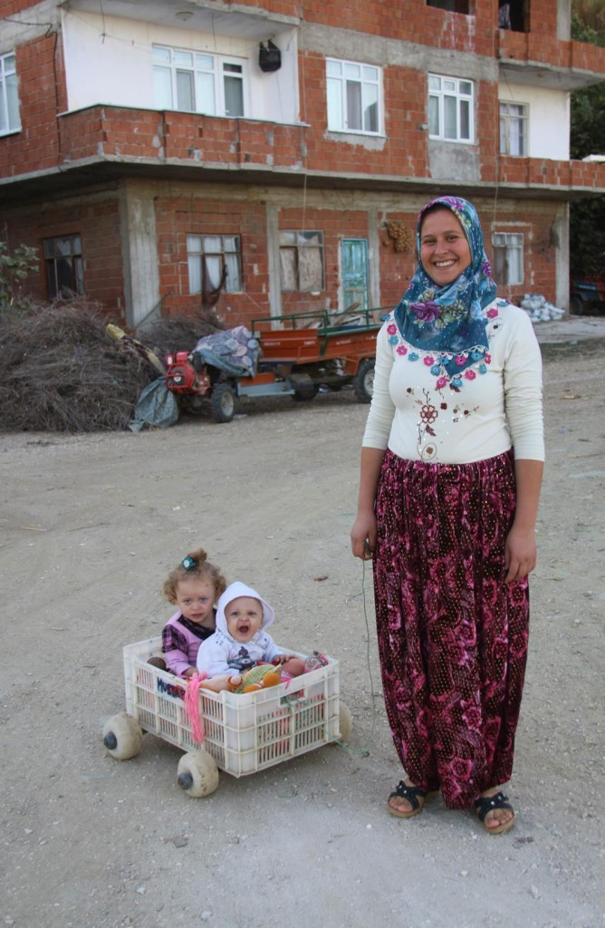 A Very Proud and Friendly Mother with Her Sweet Children in Cart Made from a Fish Box