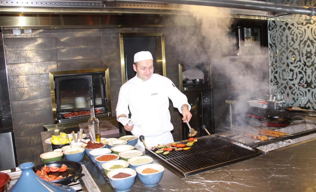 This Young Chef Happily Grilling some Vegetables and Kebabs
