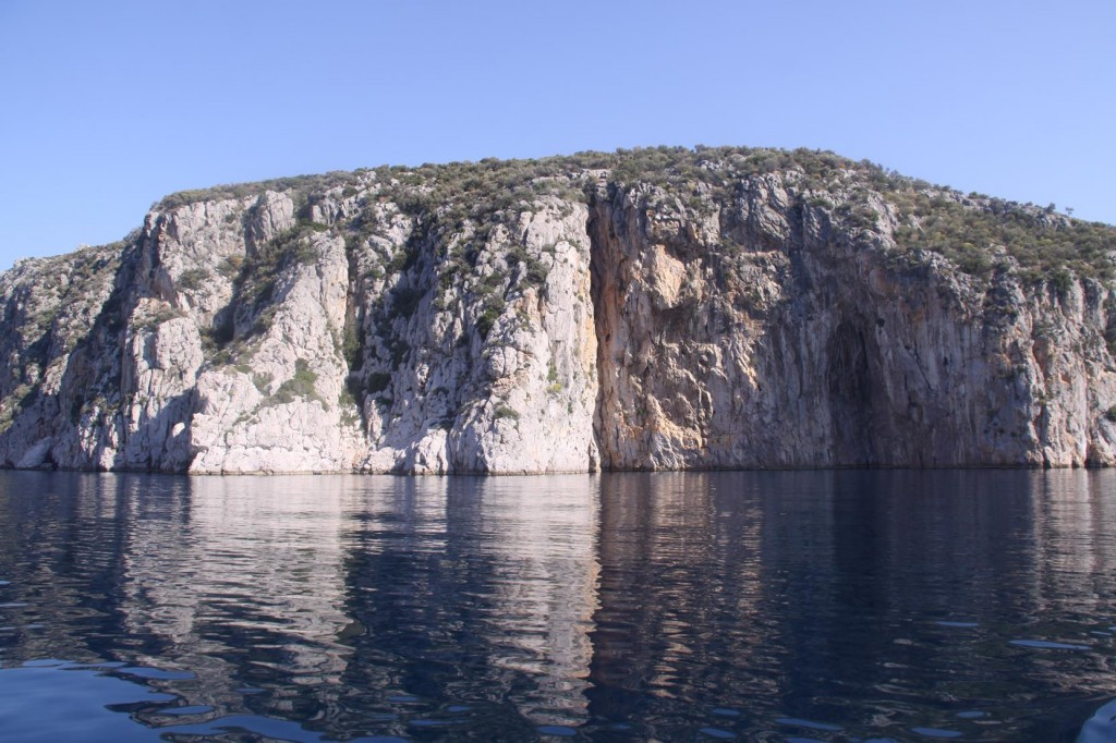 The Rugged Cliffs are Mirrored in the Calm Water