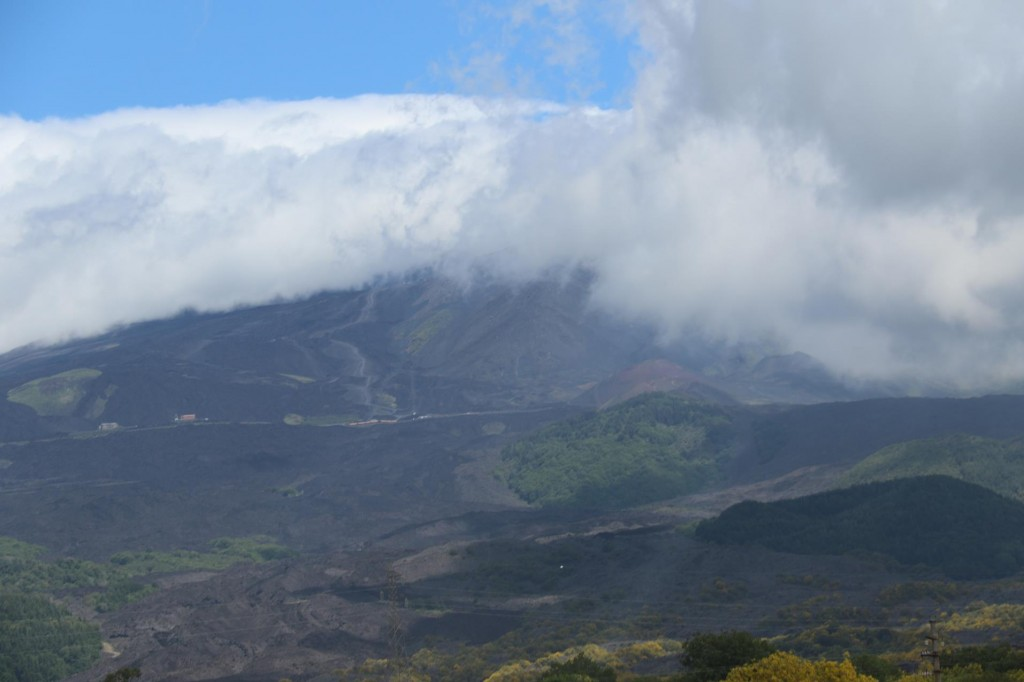 Mt Etna in the distance with a cover of smoke and clouds