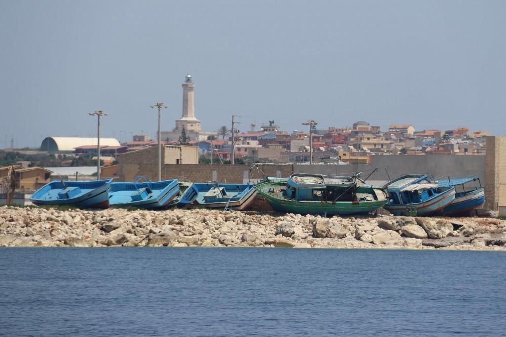 Abandoned assylum seeker boats on the shore nearby