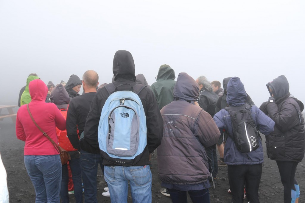 The group from the 3 buses huddled together trying to listen to the tour guides above the howling wind!