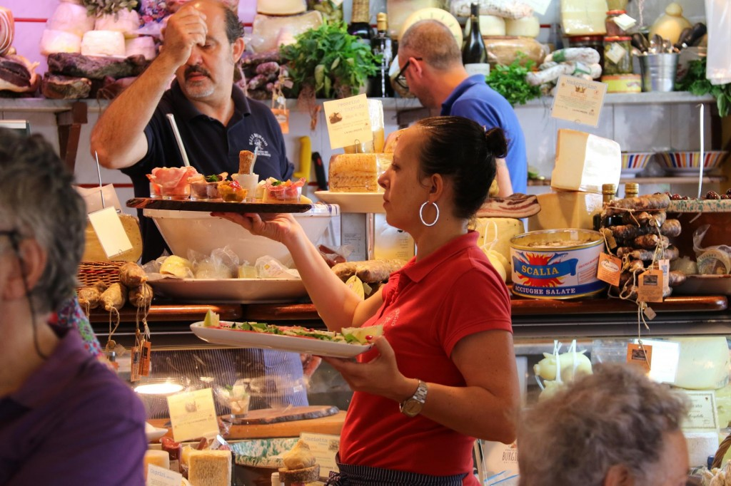 Wine and antipasto platters of cured meats, fish, cheeses and vegetables etc are served to the waiting lunch crowds