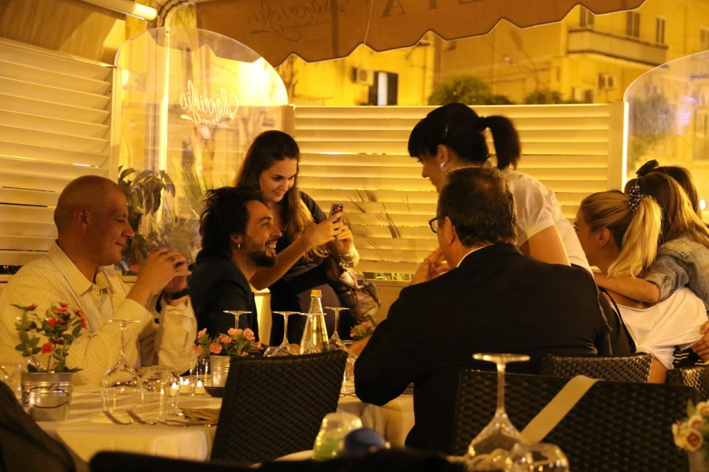 A popular Italian singer from Milan, his very attractive pregnant wife and a few others were dining in the restaurant at a table nearby