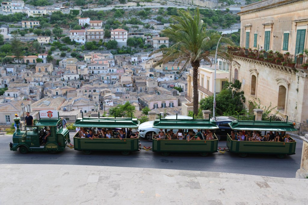 A small train full of tourists are lucky enough to get a unique opportunity of photographing a Sicilian wedding party descending from the Cathedral!