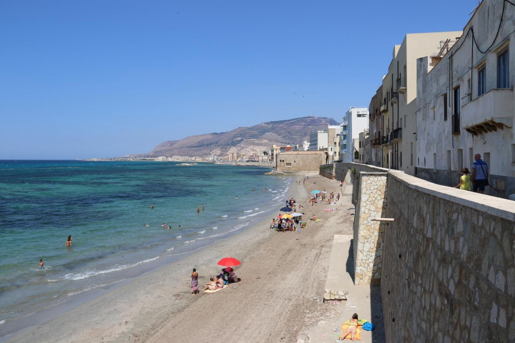 The freshly graded beach by the ancient city walls has many sunbathers enjoying the  still and warm weather