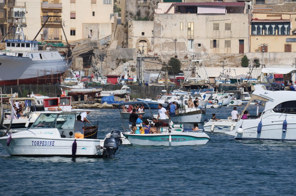 During the late afternoon there are many small boats crowding into the small bay nearby in the port