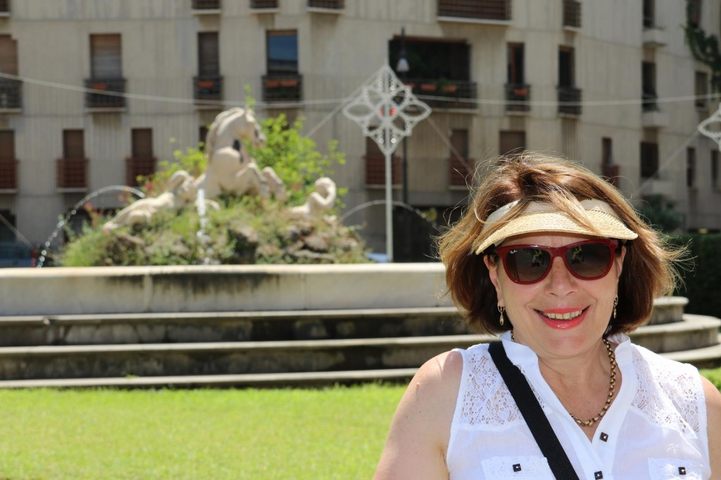 Susie in front of a fountain of white horses near Porta Felice