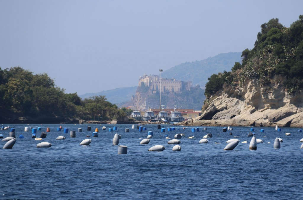 The castle on Procida Island appears in the distance through the entrance to the almost landlocked Port Miseno