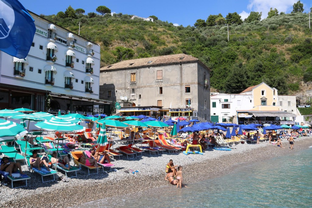 There are many families enjoying the lovely warm weather on the beach here by Nerano