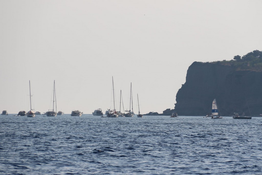 Numerous yachts and motorboats are on anchor by the port