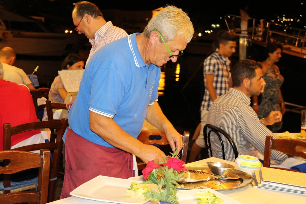 One of the very friendly owners of Riva Destra Ristorante bones the delicious looking fish for an other table