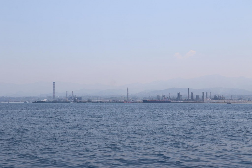 Through the haze the chimney stacks of the power station east of Milazzo can be seen as we near the coast