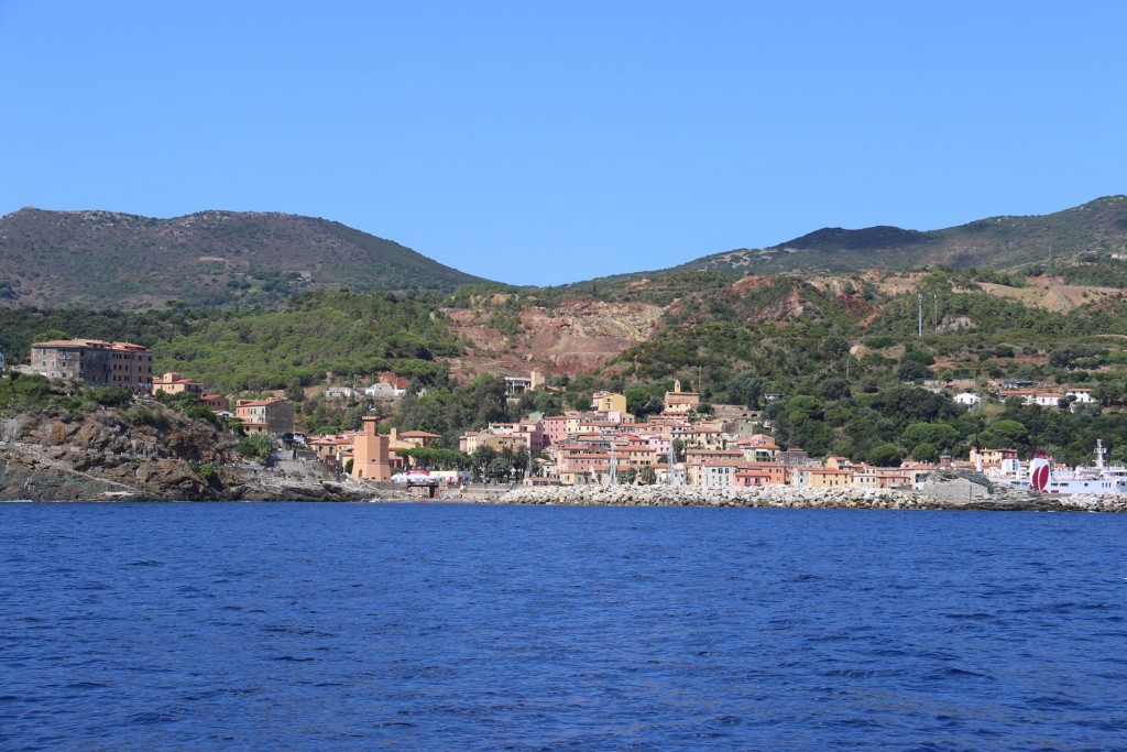 We approach the small port of Rio Marina which has noticable scars of past mining behind the town