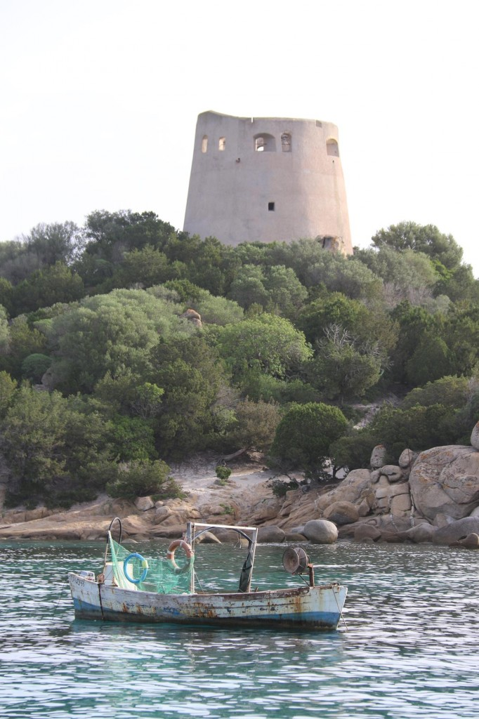 The lonely fishing boat looks dwarfed by the conspicuous old tower on the point at Cala Pira