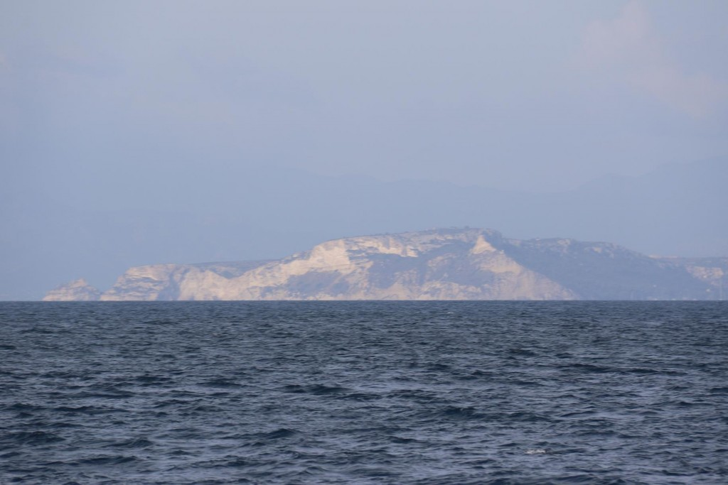In the far distance the sun is shining on the south west cape by the capital city of Sardinia called Cagliari