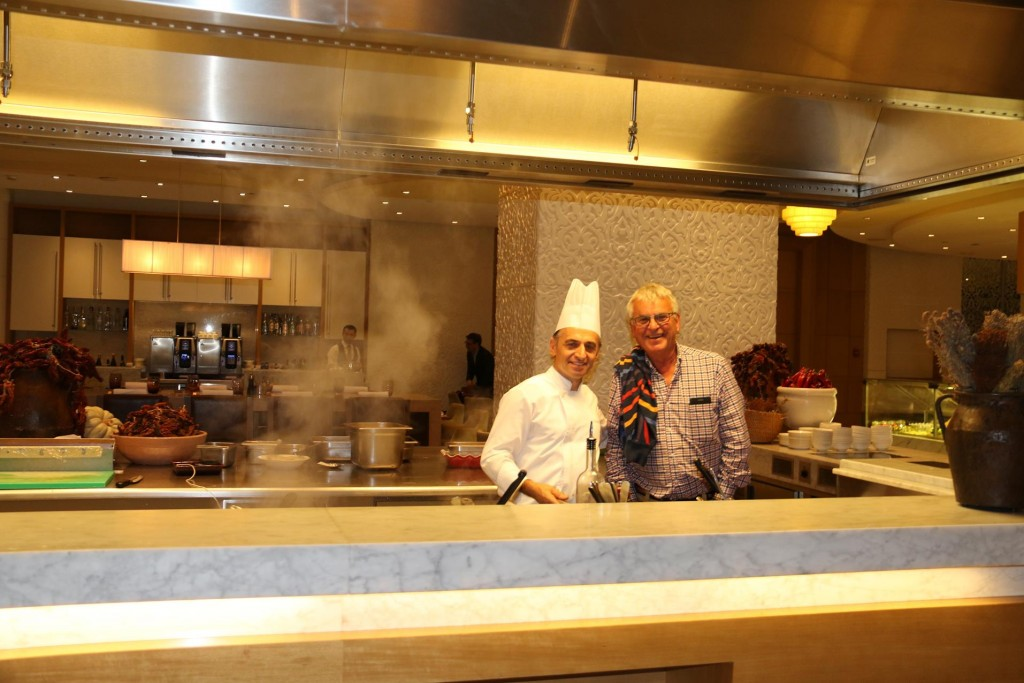 Ric talks to one of the chefs in the open kitchen in the restaurant