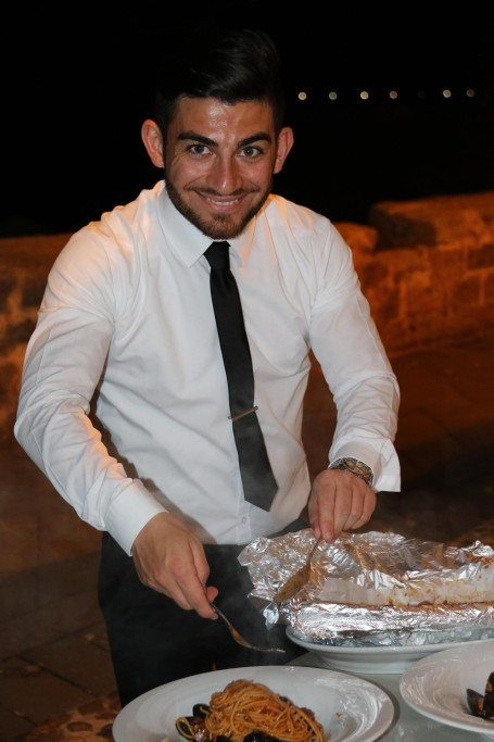 The friendly young waiter brings us some baked spaghetti with seafood