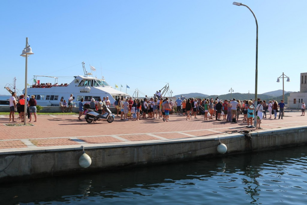 After 3 days of wind in northern Sardinia a crowd of tourists assemble to go to the La Maddelena Islands for the day on one of the many ferries leaving from Cannigione