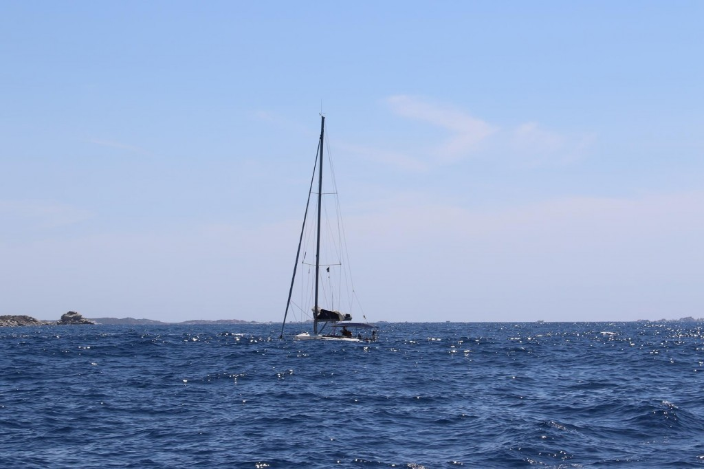A passing yacht almost buried in the big swell
