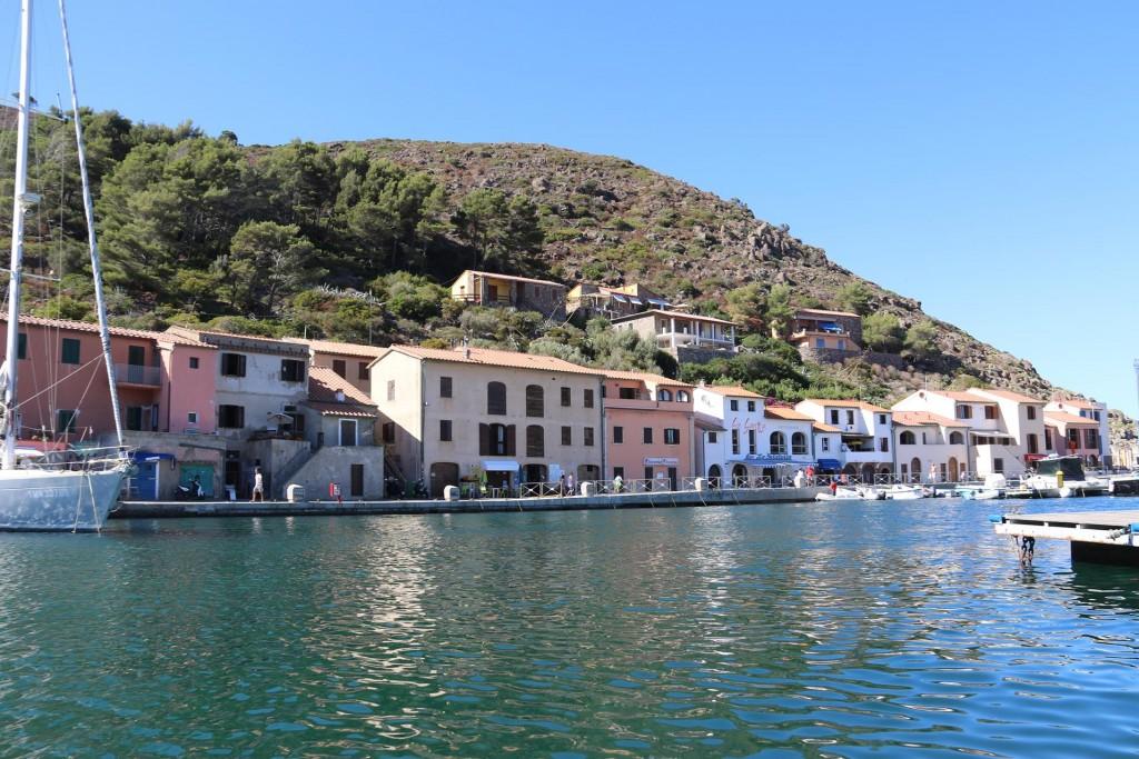 Pretty pastel coloured houses line the foreshore of Porto Capraia