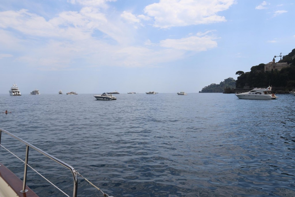 A number of large and small boats are moored nearby off Portofino