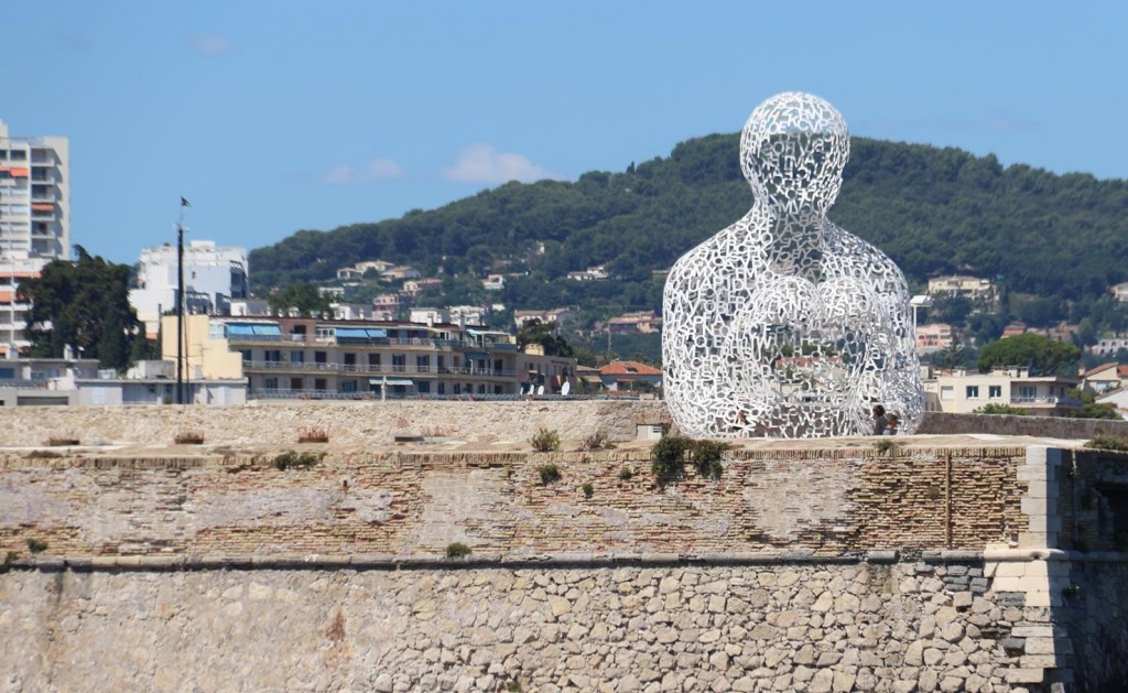 A modern sculpture overlooks the sea by the town