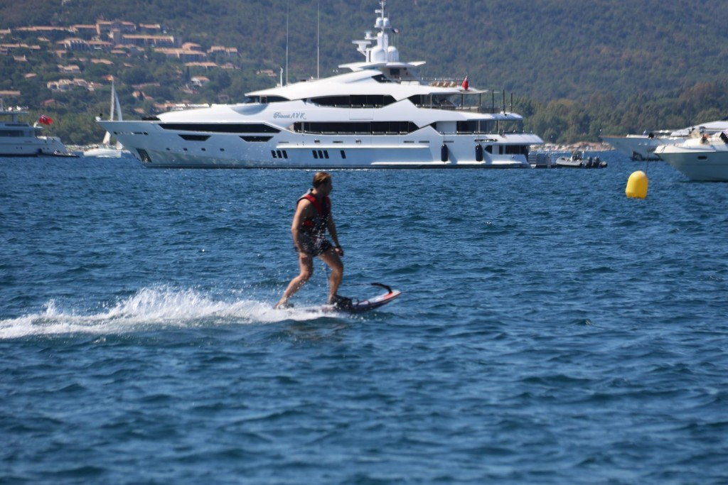 A motorized wave board rider zips around the moored boats