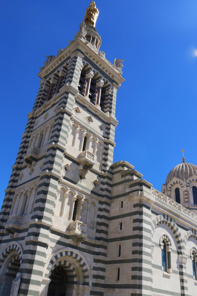 The belltower of the Notre Dame de la Garde with the gold Virgin Mary can be seen from all of Marseille