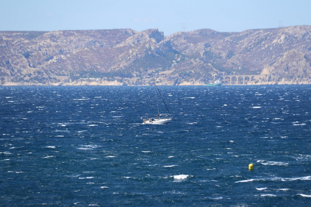 The mistrale is still blowing strongly as a boat makes it's way towards the port