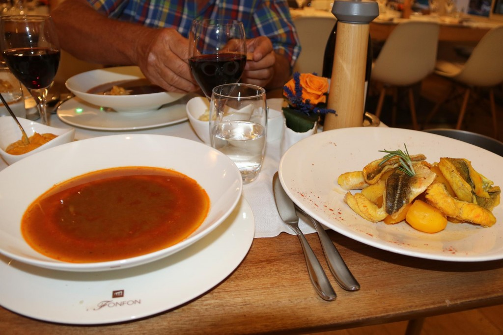The rich bouillabaisse broth and cooked fish arrive