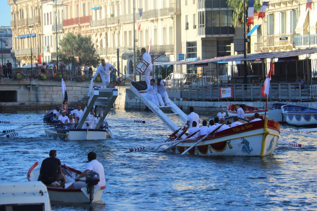 Water jousting is an ancient water sport where 2 boats with oarsmen and a jouster standing on a raised platform at one end with a pole and a shield in hand. The boats approach one another and the jousters attempt to knock each other off with the poles into the water
