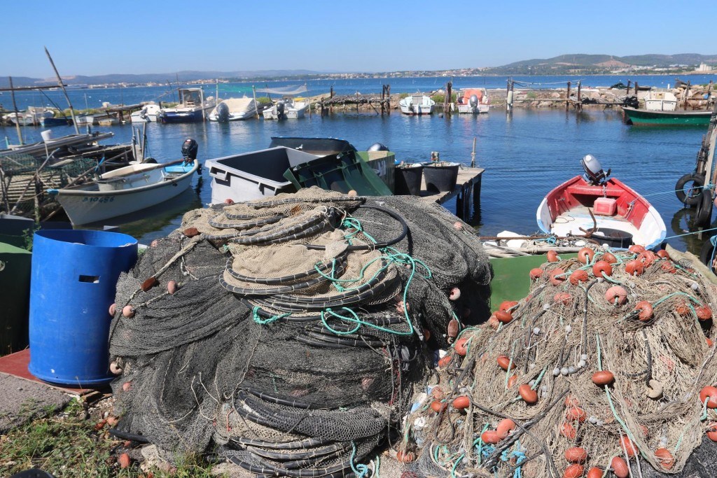 Piles of nets lie all around the shore and are draped over fences in the tiny harbour