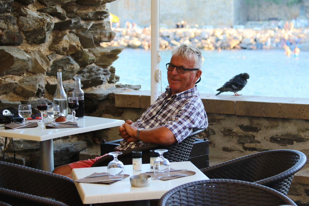 Ric with feathered friend  nearby, takes a table on the side, nicely sheltered from the wind overlooking the water